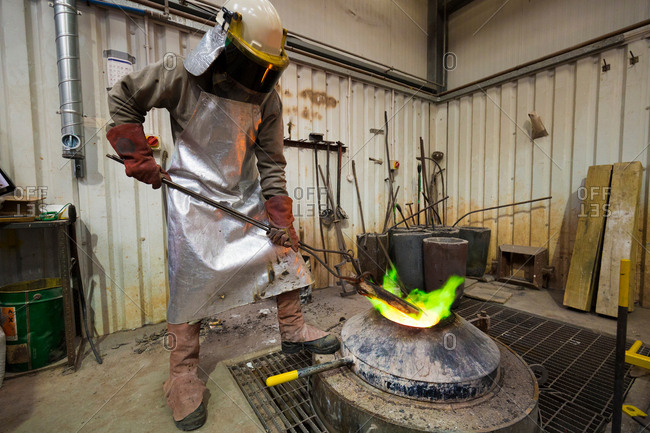 Male foundry worker heating bronze ingot over furnace in bronze foundry