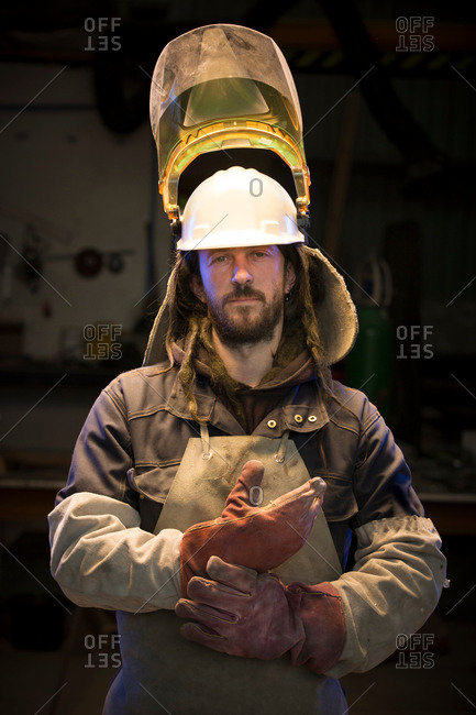 Portrait of mid adult male foundry worker putting on protective gloves in bronze foundry
