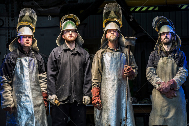 Portrait of four male foundry workers wearing protective clothing in bronze foundry