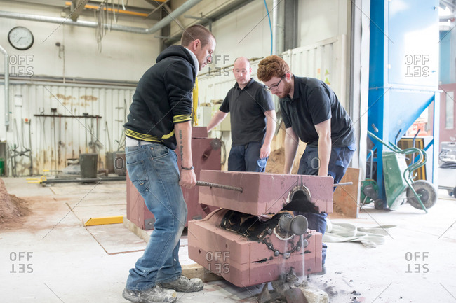 Male foundry workers lifting mold from bronze sculpture in bronze foundry