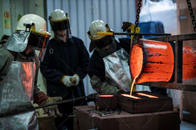 Male foundry workers pouring bronze melting pot in bronze foundry