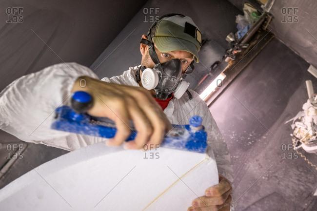 Male carpenter using carpentry equipment on surfboard in surfboard maker's workshop