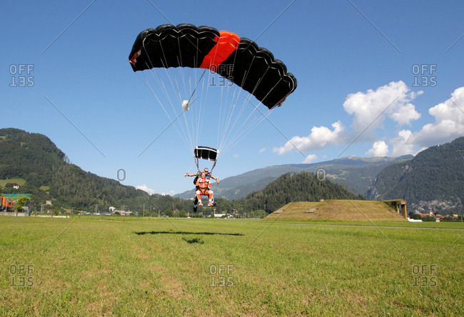 Tandem sky divers landing in field with parachute, Interlaken, Berne, Switzerland