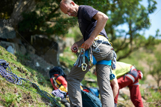 Rock climber on hillside preparing climbing equipment on safety harness
