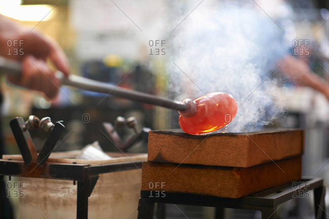 Molten glass material being shaped on blowpipe in workshop