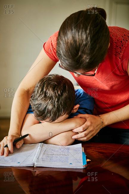 Mother comforting upset son doing homework