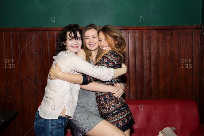 Three adult female friends having group hug in bar