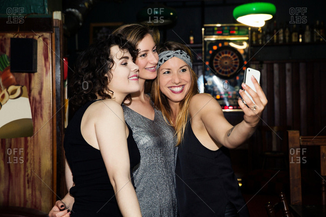 Three adult female friends taking smartphone selfie on night out in bar