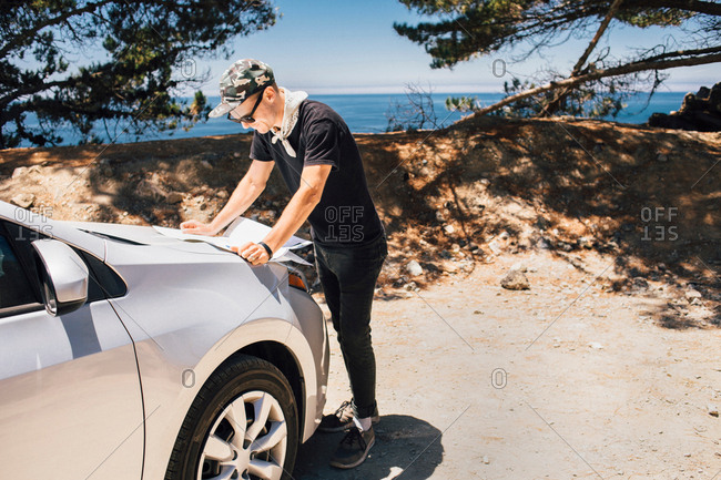 Man on road trip reading map on car hood, Big Sur, California, USA