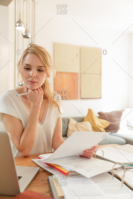 Woman with paperwork looking at laptop