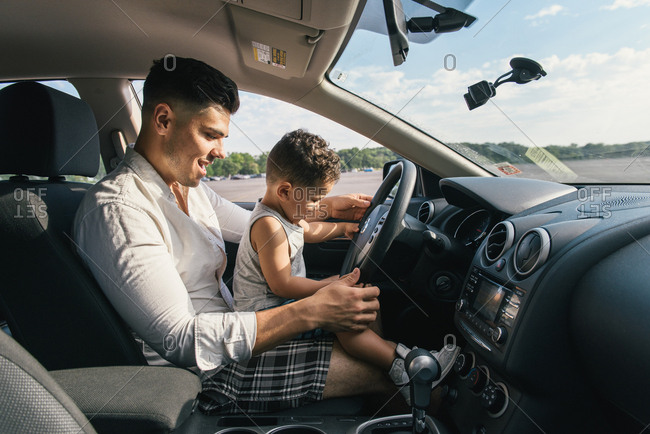 Male toddler sitting on father's knee driving car in Pelham Bay Park, Bronx, New York, USA