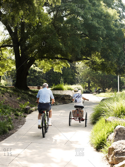 Rear view of senior cycling couple cycling in park