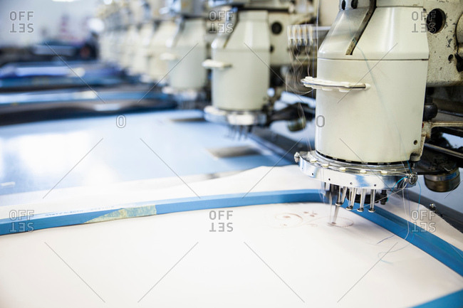 Rows of programmed embroidery machines speed stitching white cloth in clothing factory