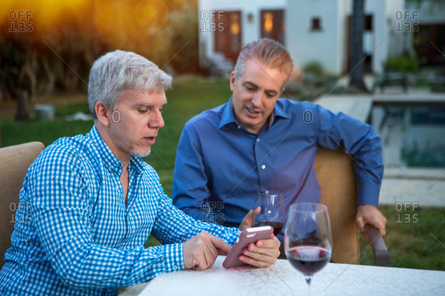 Two mature men using smartphone at garden party table
