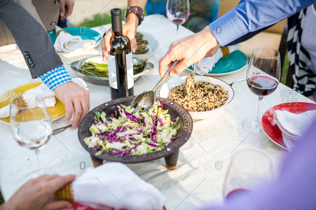 Cropped shot of adult friends helping themselves to food and drink at garden party table