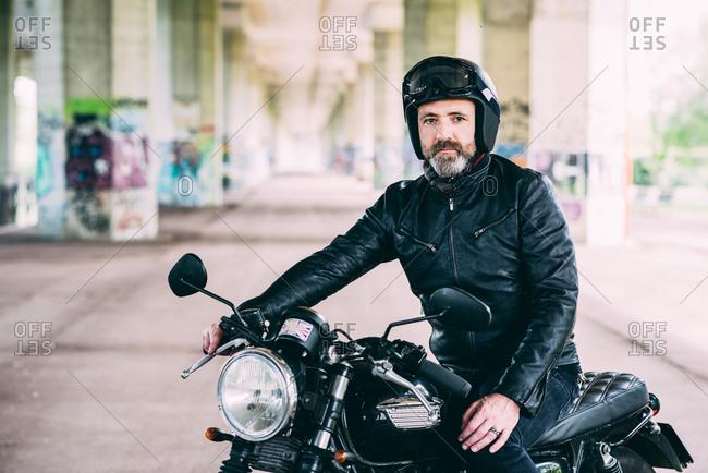 Mature male motorcyclist sitting on motorcycle wearing crash helmet under flyover