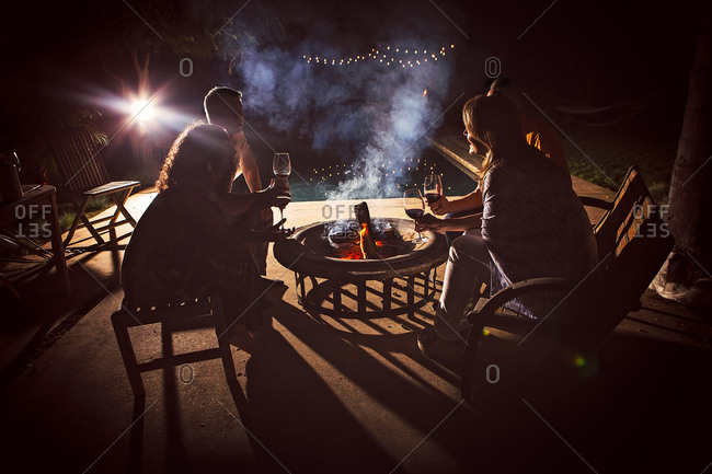 Four mature adults sitting together around patio fire at night
