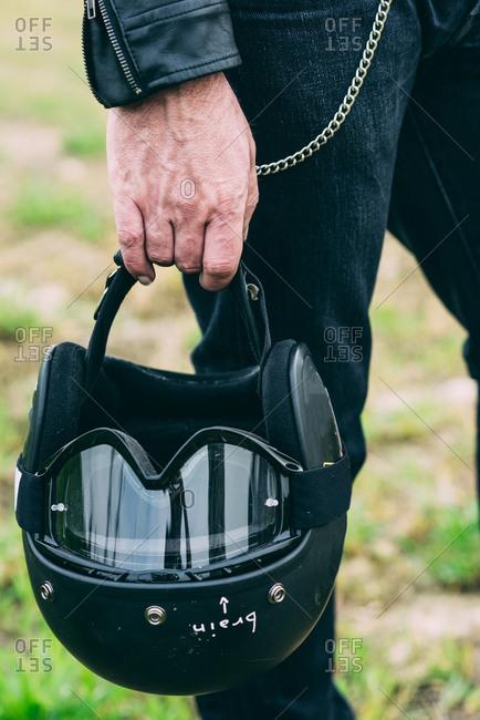 Hand of male motorcyclist holding black crash helmet