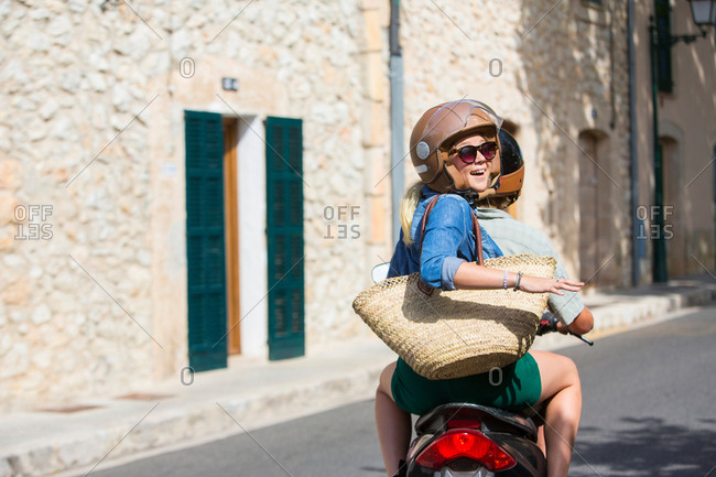 Young woman riding pillion through village looking back, Majorca, Spain