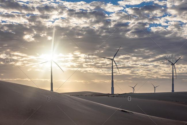 Wind turbines in desert landscape at sunset, Taiba, Ceara, Brazil
