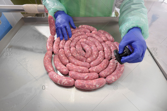 Worker making Italian sausages in sausage factory, close-up