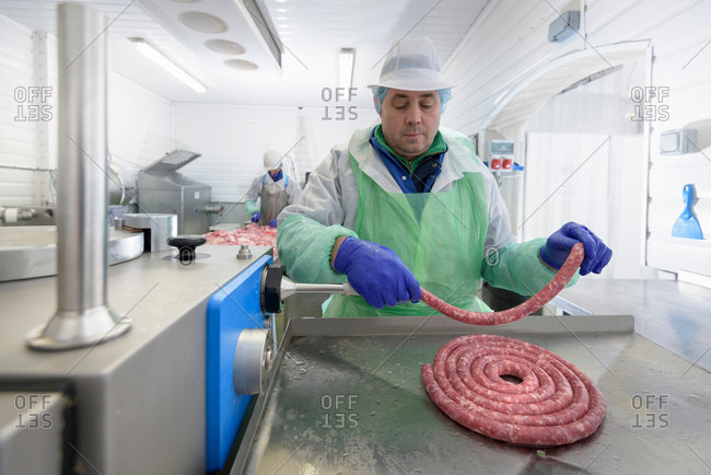 Worker making Italian sausages in sausage factory
