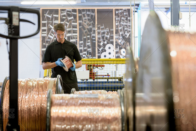Worker inspecting copper cable in cable factory