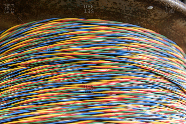 Multicoloured cable on reel in cable factory, close up
