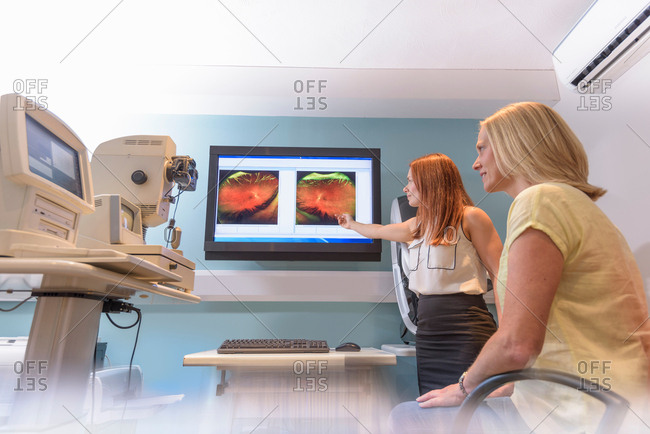 Optician discussing images of inside of patient's eyes at small business opticians