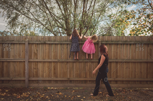 Girls peeking over a fence while their mother looks on
