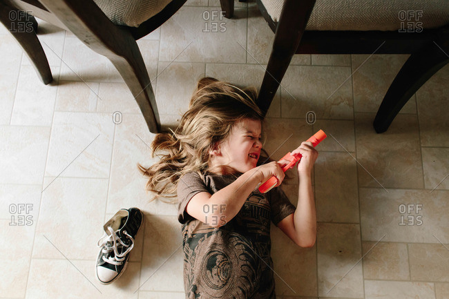Boy lying down on the floor playing with a toy gun