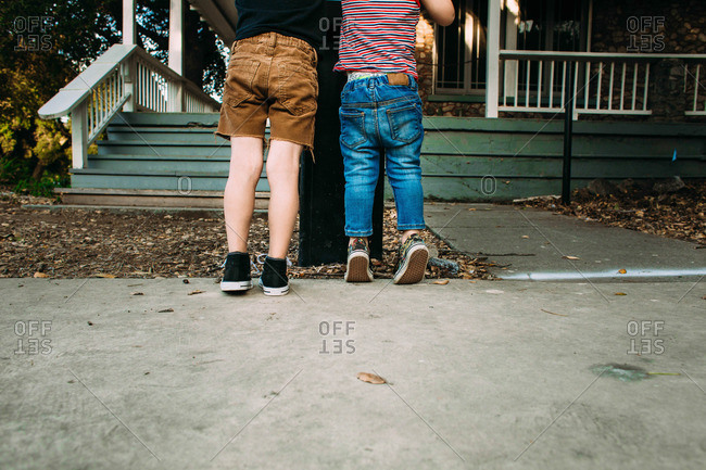 Two boys standing side-by-side on tiptoe