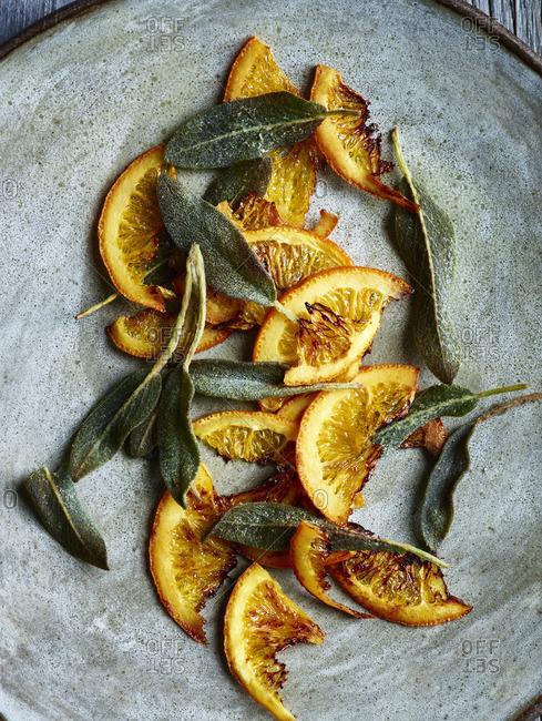 Roasted garnish of orange slices and sage leaves on stone platter