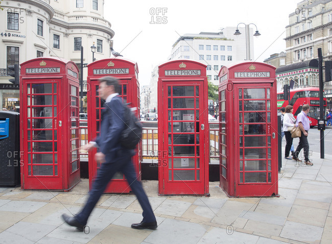 London, England - September 19, 2016: Businessman walking past row of red telephone booths