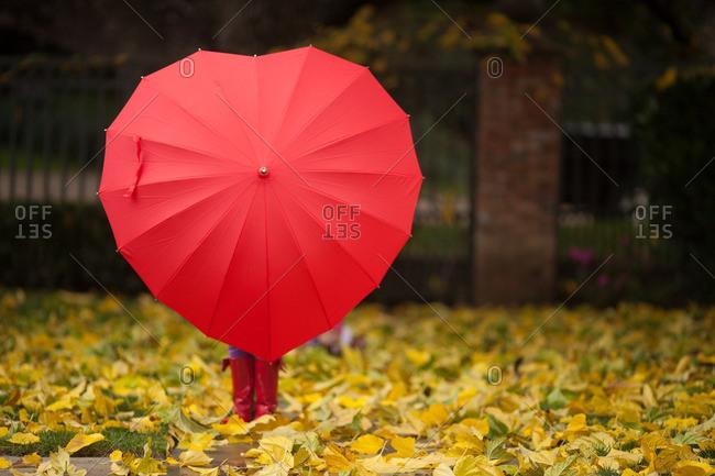 Child holding heart shaped umbrella