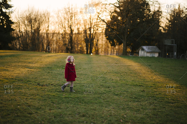 Girl wander rural yard in coat
