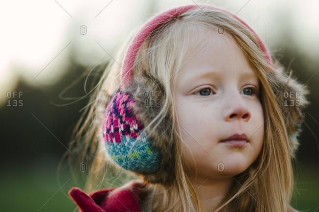 A girl outside in earmuffs