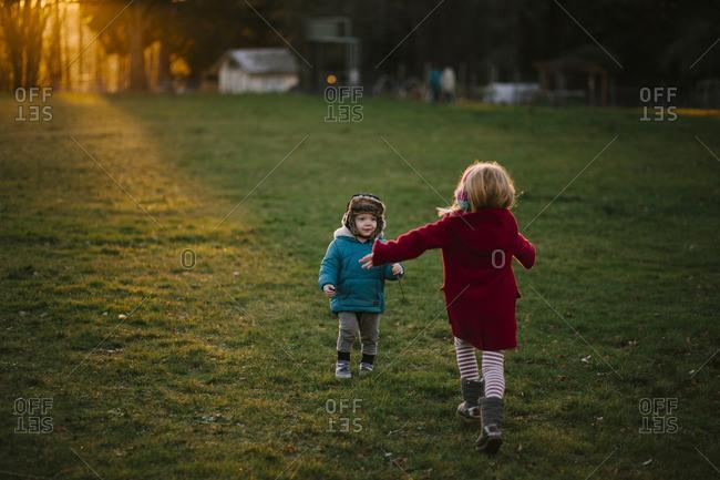 Siblings in chilly rural yard