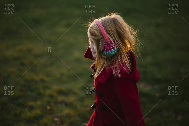 Girl in earmuffs in sunny yard