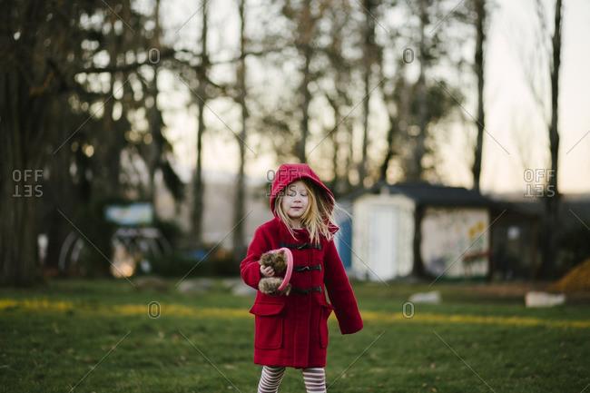 Girl carrying her earmuffs in yard