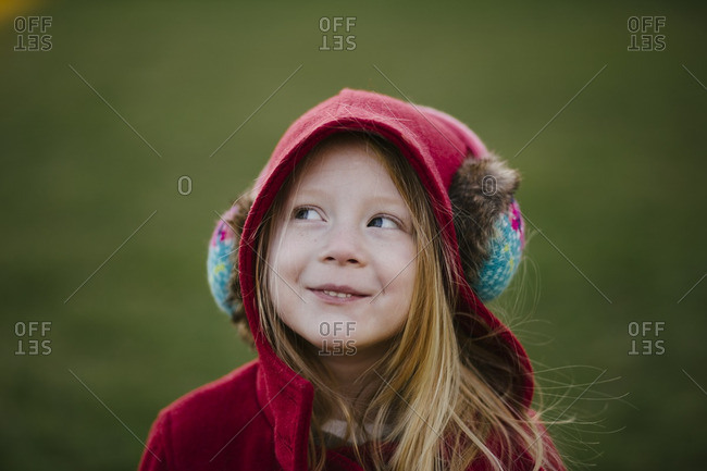 Girl in earmuffs smiling outdoors