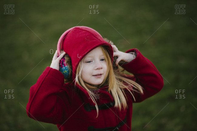 Girl putting on earmuffs outside