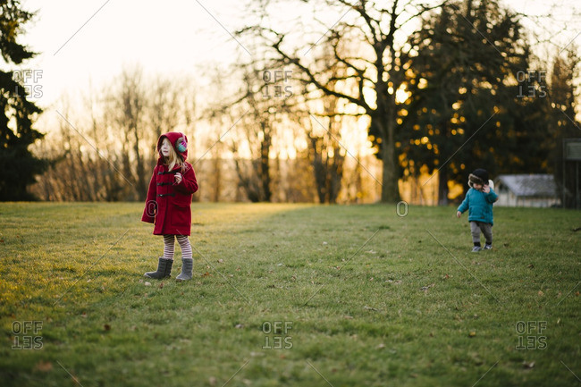 Siblings in cold rural yard