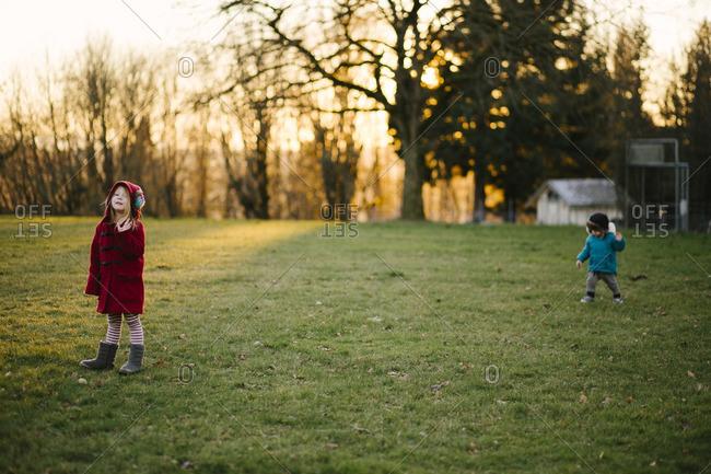 Siblings in a cold rural yard