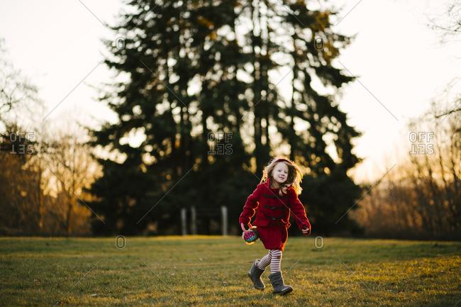 Girl running in chilly yard