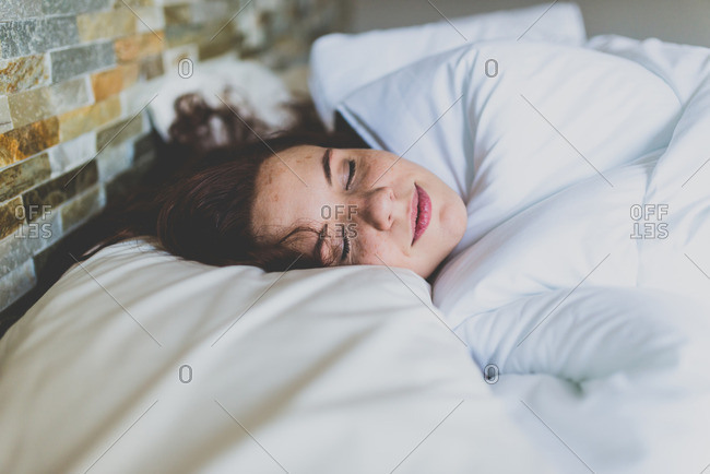 Woman nestled in soft bed