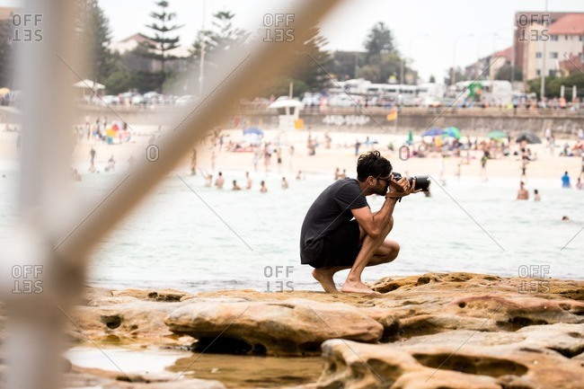 Bondi Beach, Australia - September 22, 2016: Man taking photos at crowded beach