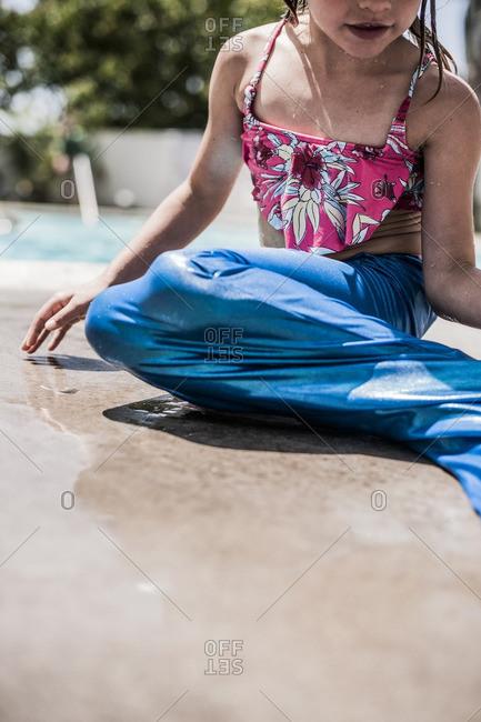 Little girl sitting poolside wearing a mermaid tail