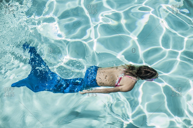 Young girl swimming underwater wearing a mermaid tail