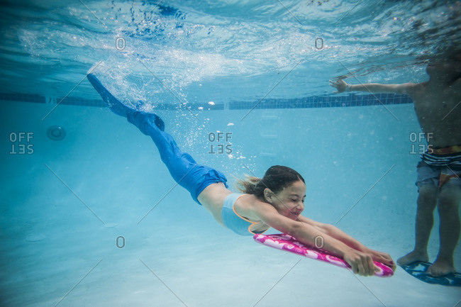 Little girl swimming underwater wearing a mermaid tail with kickboard